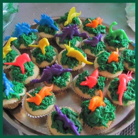Cupcake met botercreme (groen(kleurstof)) en een gekleurde dinosaurus